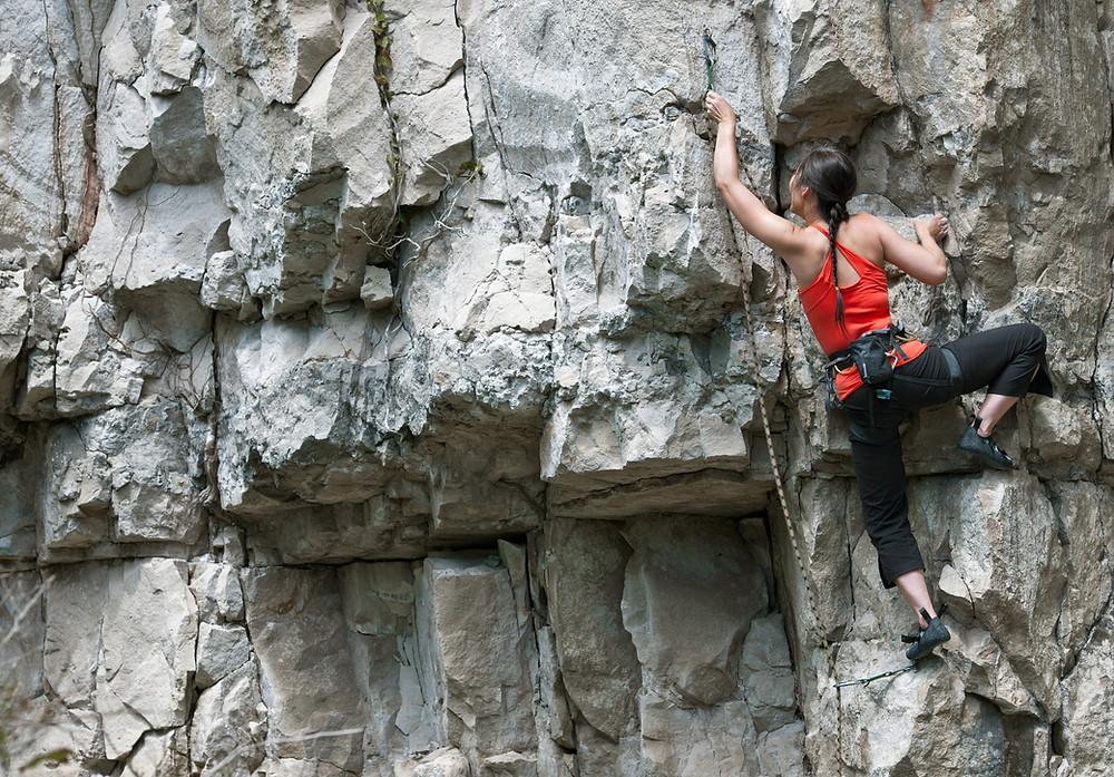 A rock climber scaling up a rock face