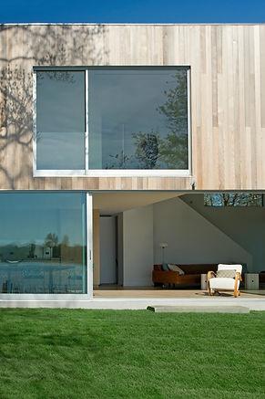 Modern living room large sliding glass doors aluminum storefront house Sag Harbor