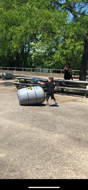 Little-Boy-Holfing-Laser-Gun-Beside-Inflatable-Obstacle.jpg