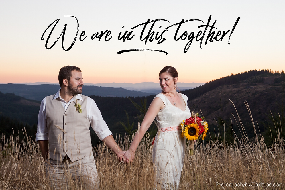 Couple stands together holding hands in solidarity at the top of a mountain at sunset on their wedding day.