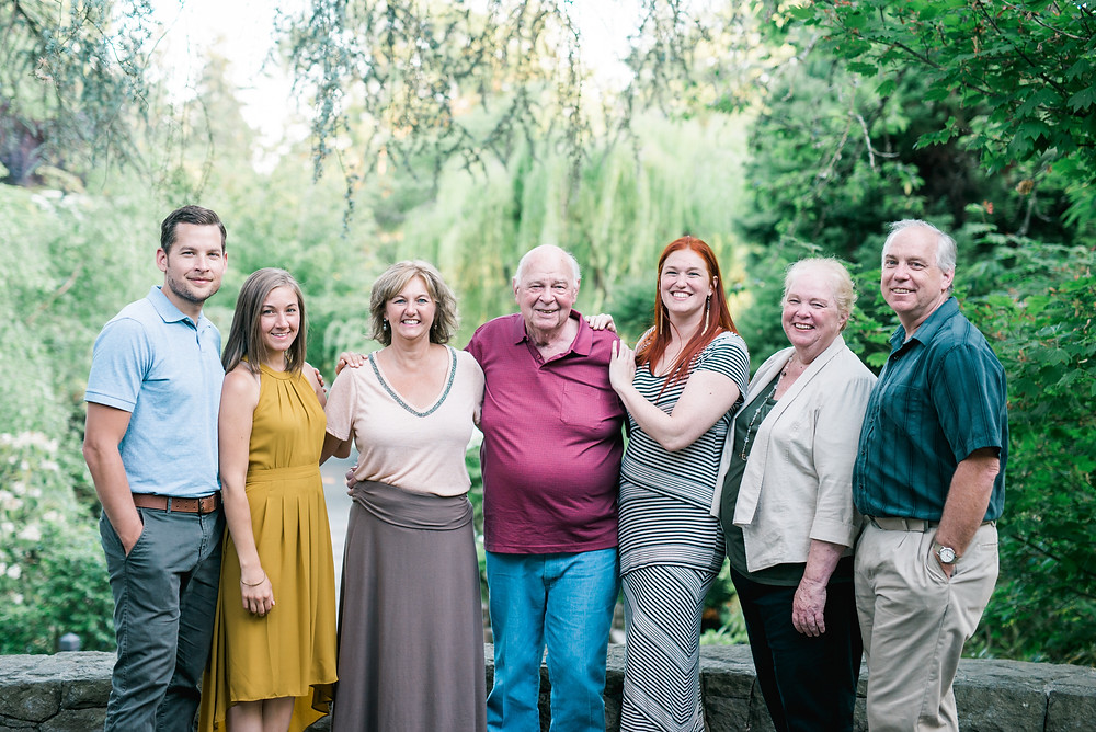Group photo of Cambrae's family standing togoether arms wrapped around each others shoulders. Taken at Crystal Springs Rhododendron Garden.