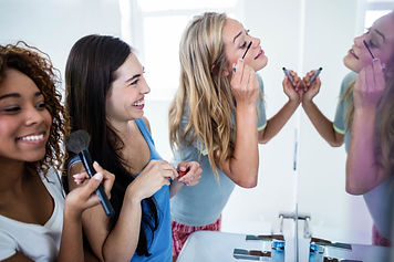 Three smiling friends putting makeup on