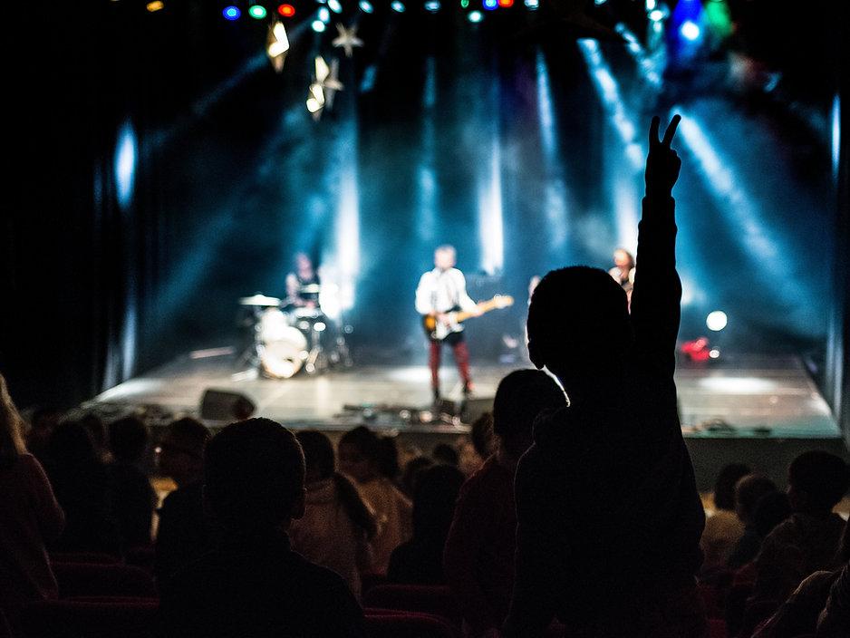 trois personnes, musicens, deux hommes et une femmme qui écoue de la musique avec un casque sur les oreilles. Ce sont des rockeurs au coeur tendre. Rico le batteur a des tatouages sur les bras, lucien porte des badges sur sa veste et géraldine la belle chanteuse le regarde en souriant