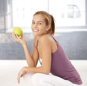 Portrait of happy squatter girl on scale holding green apple, laughing at camera._.jpg