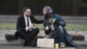 Businessman eating and talking with poor homeless man on pavement..jpg