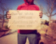 a homeless person with a sign toned wit
