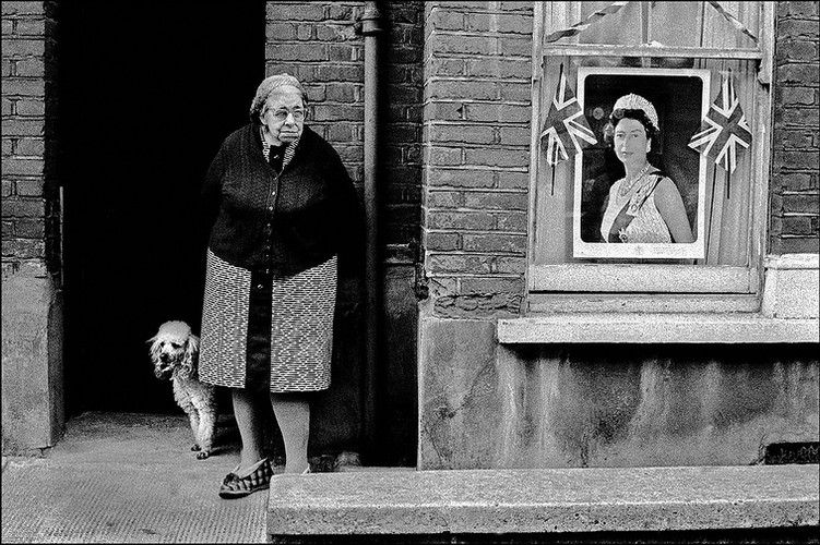 欧洲,英格兰,伦敦。女王钻石禧年期间,一位年老的女人和狗站在家门口,前窗上挂着女王肖像和英国米字旗 | 伊恩·贝瑞 | 1977