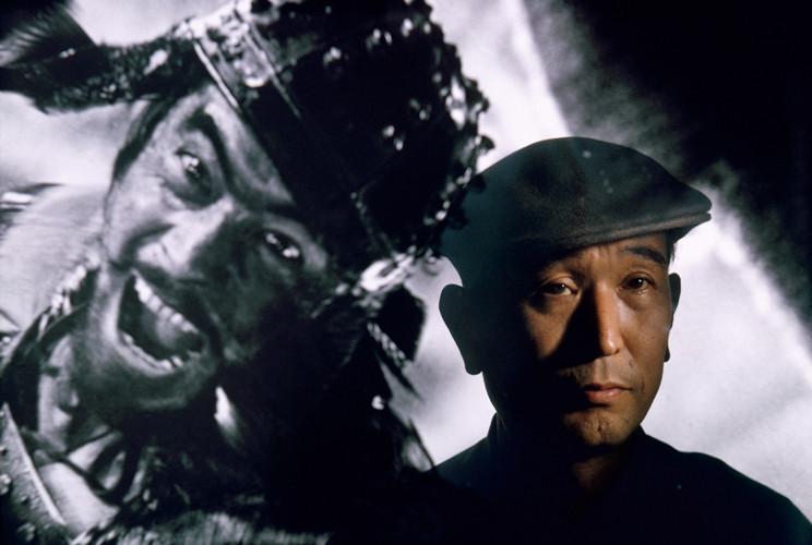 Film director Akira Kurosawa standing before an image of his principal star, Toshiro Mifune, Tokyo | Brian Brake | 1963