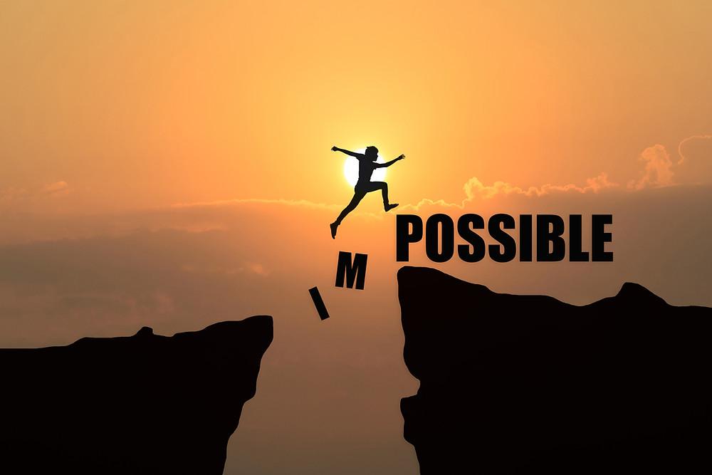 """Eine Person, die Silhouette vor der Sonne, springt von einer Felsnase zur anderen, darunter eine tiefe Schlucht und der Schriftzug """"Impossible"""". Das """"Im"""" von Impossible bricht auseinander, so wird aus dem Impossible ein Possible."""