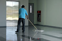 Janitor providing commercial cleaning services like mopping, vacuuming, and sweeping.
