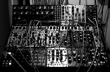Modular synthesizer with four rows of modules installed. Some messy cabling connects several of the modules. You too can play the synth shown in this picture. (Seriously!)