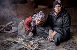 Bedouin woman and her daughter making tea.