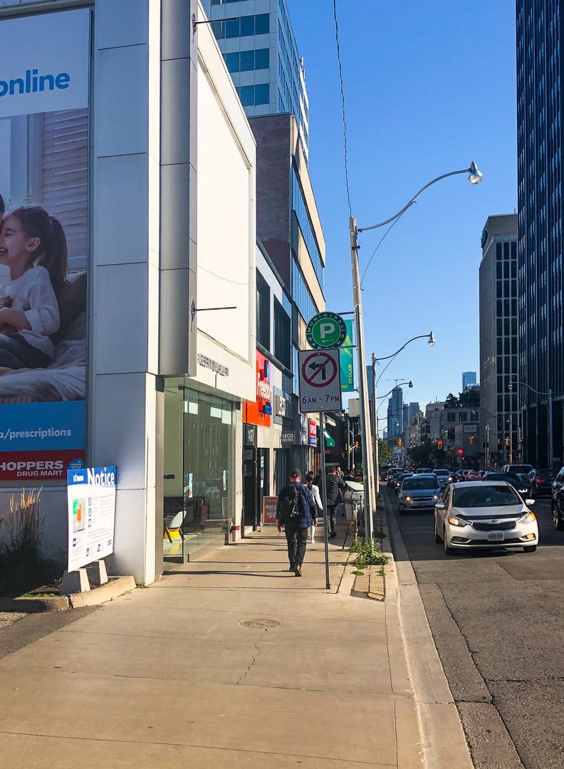 Pedestrian walking south on Yonge Street