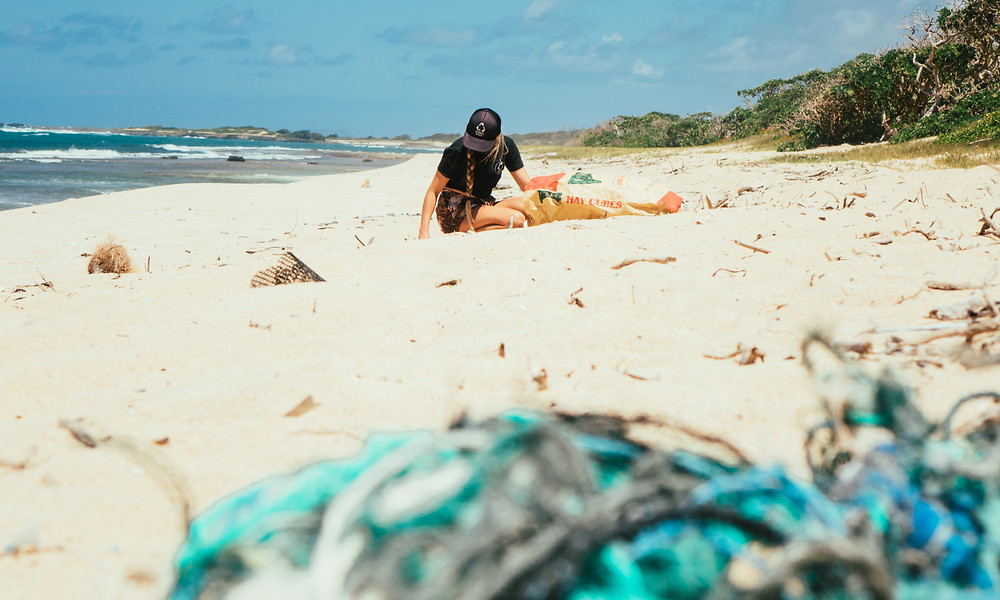 A girl is cleaning a polluted beach full of plastic alone.