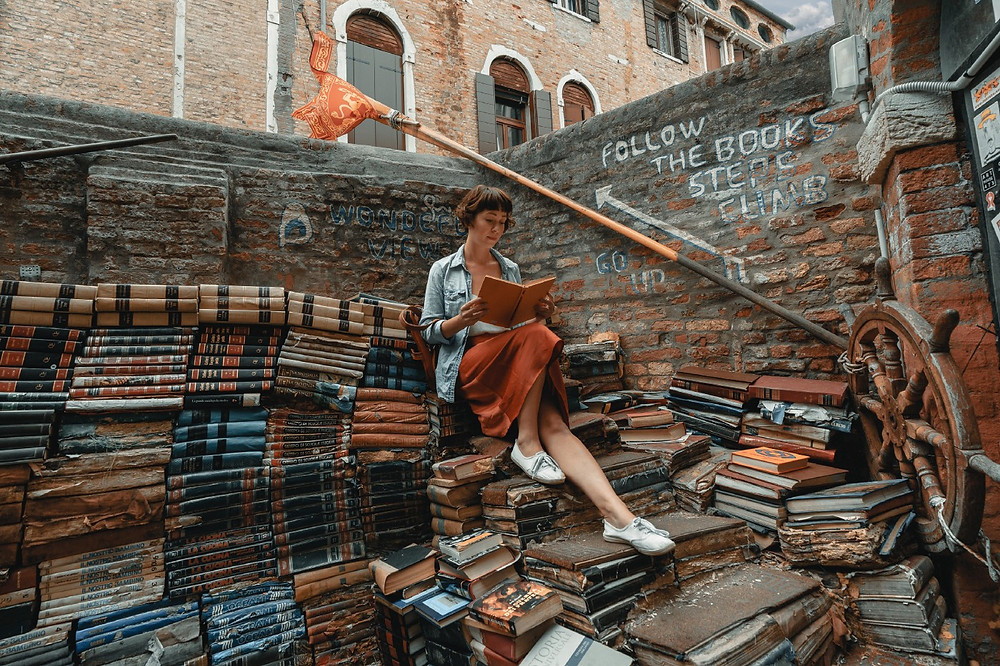 Young woman reading atop piles of old books
