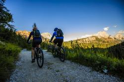 Mountain biking couple with bikes on tra