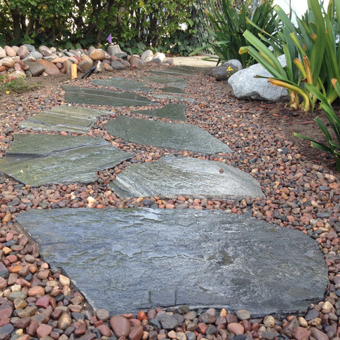 Small rocks have been placed around the flagstone path.
