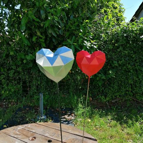 Coeur sur pic décoratif en zinc naturel et zinc naturel peint en rouge.