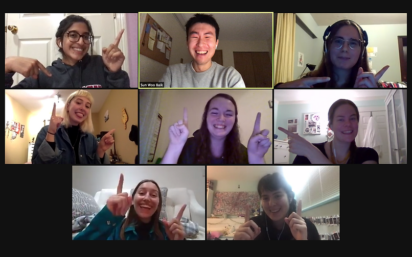 A screenshot of a Zoom video call with eight people each in their own video window. Each person is pointing to the person in the centre.