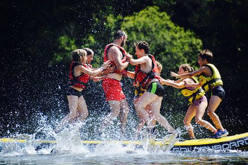 vacances en famille bien organiséesen Corrèze avec activité nautiques. tous sur un Stand up paddle géant sur le Lac des Bariousses