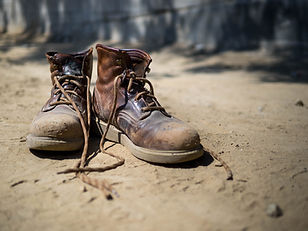 Heavily used work boots on the rough ter