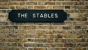 Stables sign indicating _The Stables_ on old weathered brick wall - Image.jpg