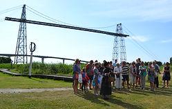 un groupe assiste à la visite théâtralisée du pont transbordeur
