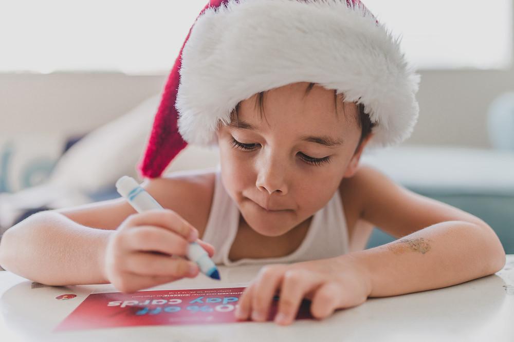 criança-com-um-gorro-de-natal-desenhando-no-cartao-de-natal