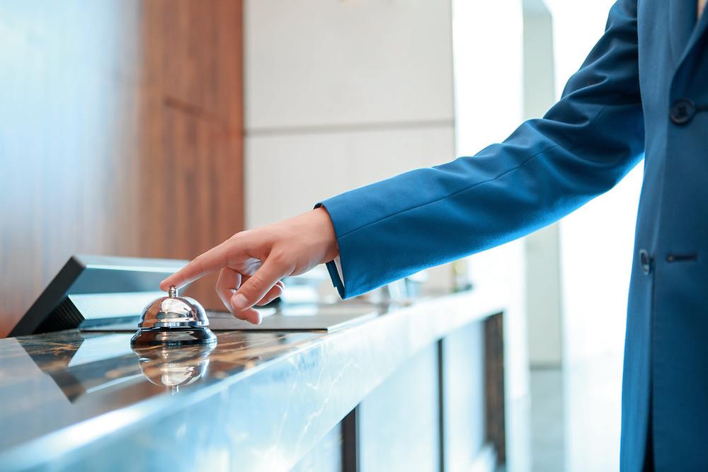 homem-tocando-campainha-de-hotel-na-recepção