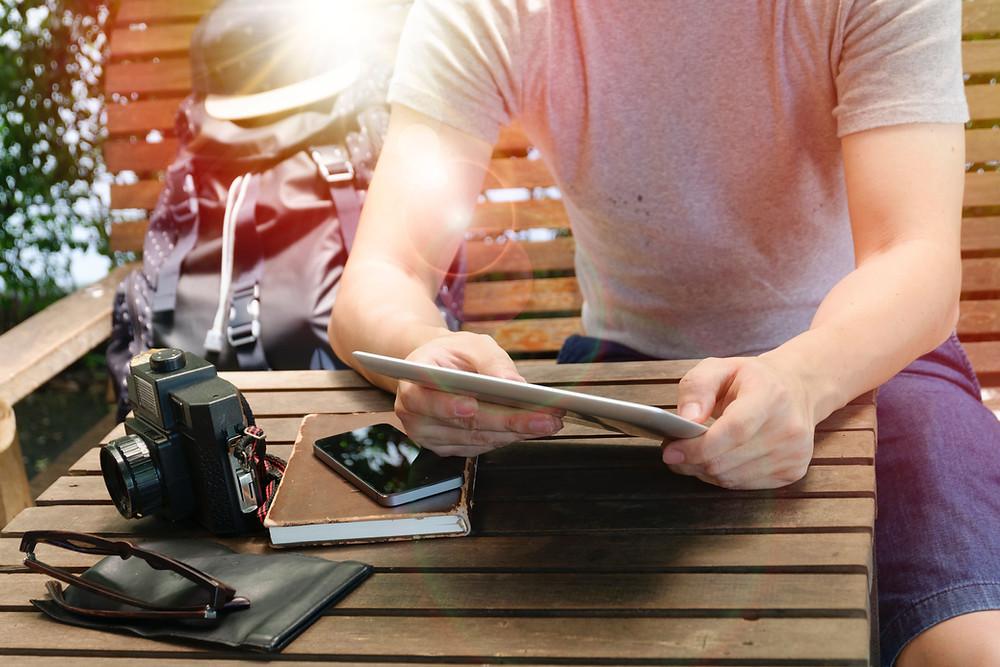 homem-com-mochila-sentado-numa-mesa-mexendo-em-um-tablet