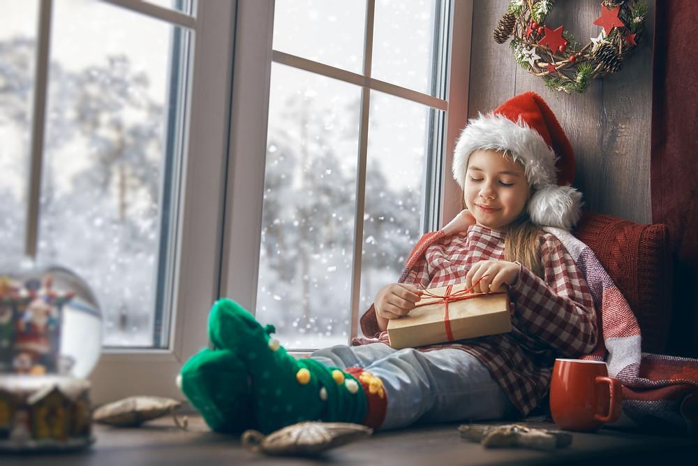menina-perto-da-janela-abrindo-um-presente-de-natal