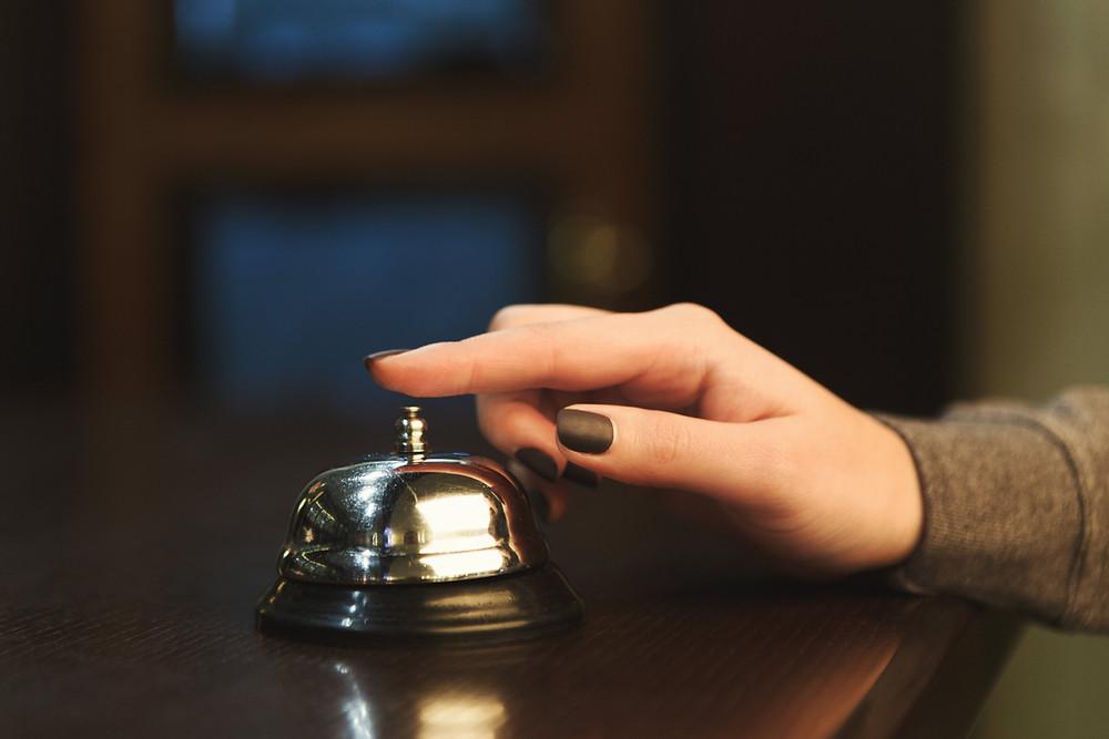 mão-tocando-a-campainha-de-recepção-de-hotel
