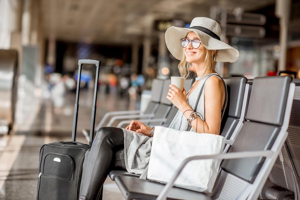 mulher-com-a-mala-esperando-no-aeroporto-estrangeiro-hospede