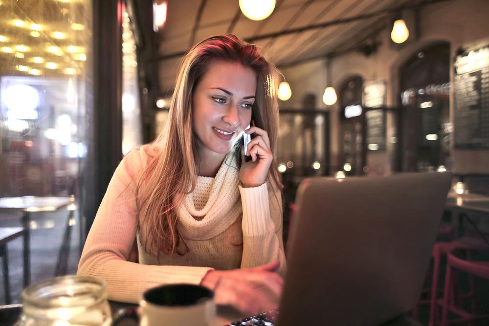 mulher-no-telefone-em-frente-ao-notebook