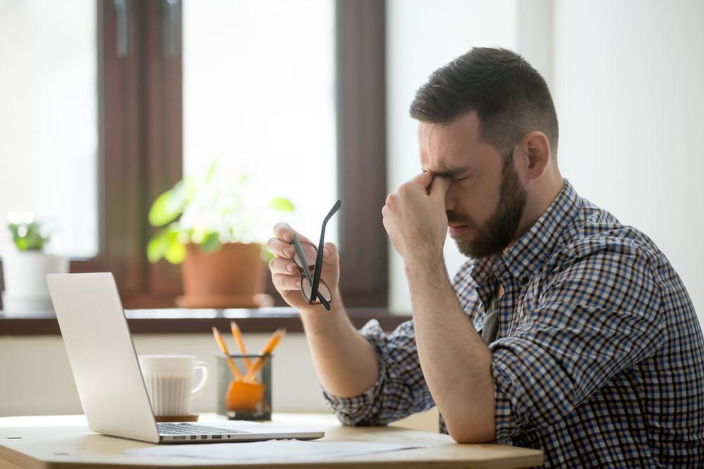 Homem-com-a-mao-no-rosto-em-frente-a-um-computador