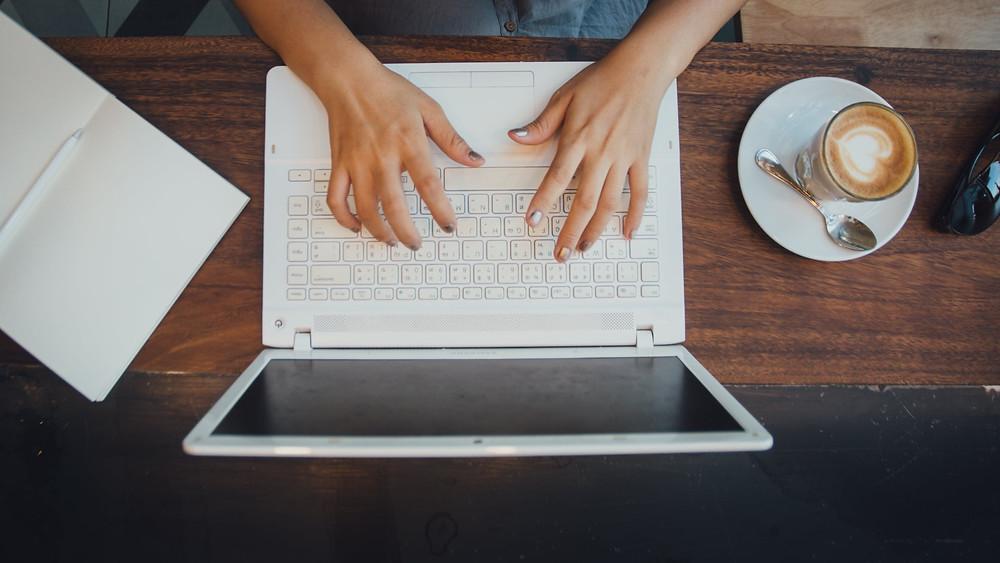 mao-digitando-no-notebook-branco-com-uma-xicara-de-cafe-do-lado