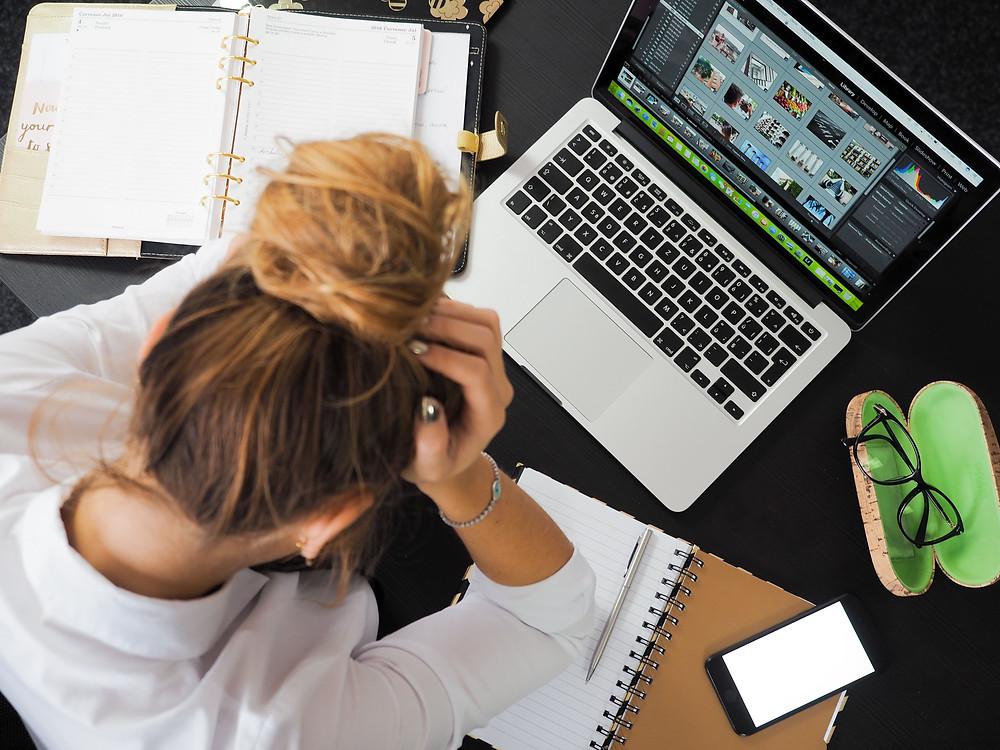 moça-com-cabeça-baixa-triste-escorada-em-cima-da-mesa-do-escritorio