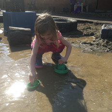 A child plays with boats in the sand area.