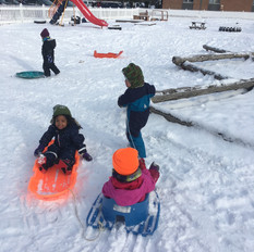 Children play with sleds in the snow.