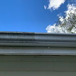 Greensboro gutter cleaning company. This image shows the before and after of the exterior gutter cleaning or restoration of the gutter.