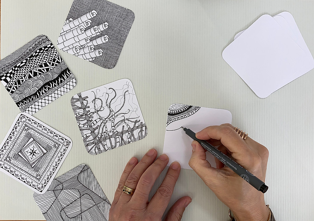 Hands drawing doodles on square paper tiles.