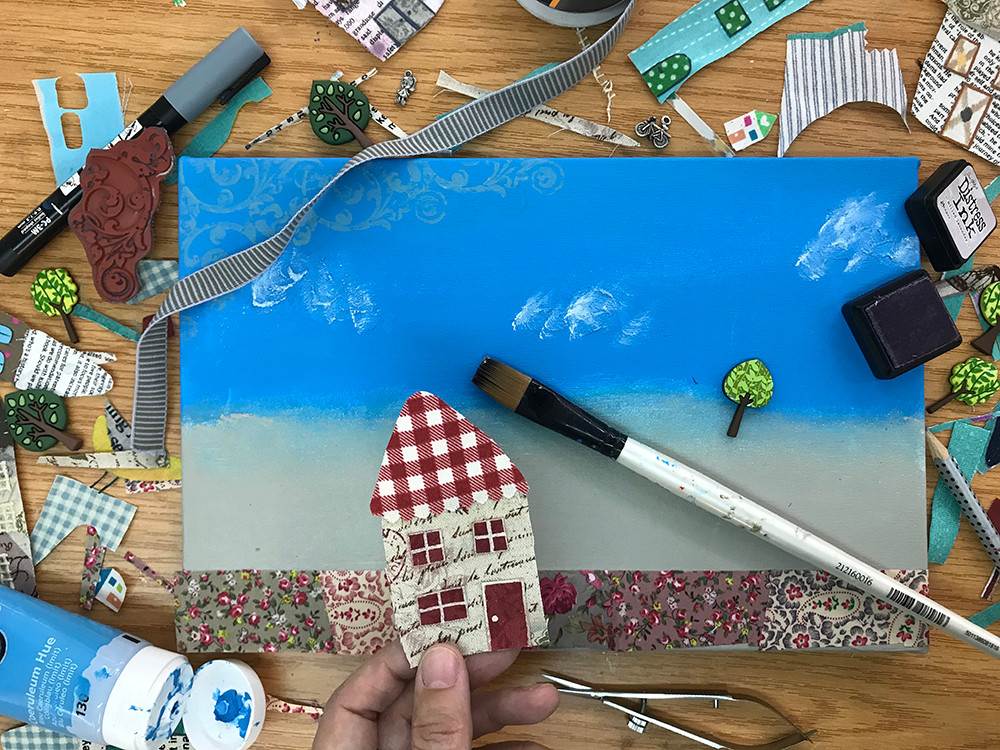 Canvas with background paint and collage art in progress. Paintbrush, paint, pens and fabric offcuts are all around the desk.
