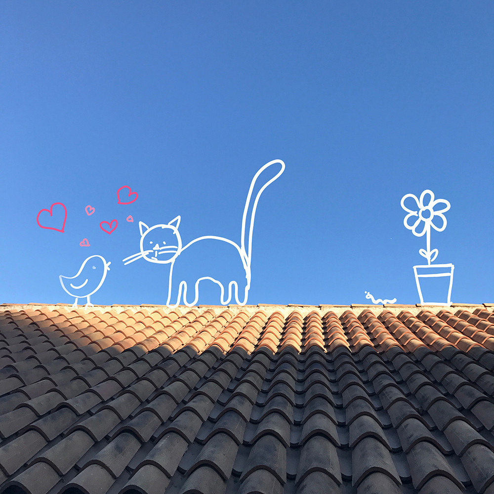A roof top against a blue sky is transformed into a whimsical scene by adding doodles. A cat and a bird fall in love on the top of the roof.
