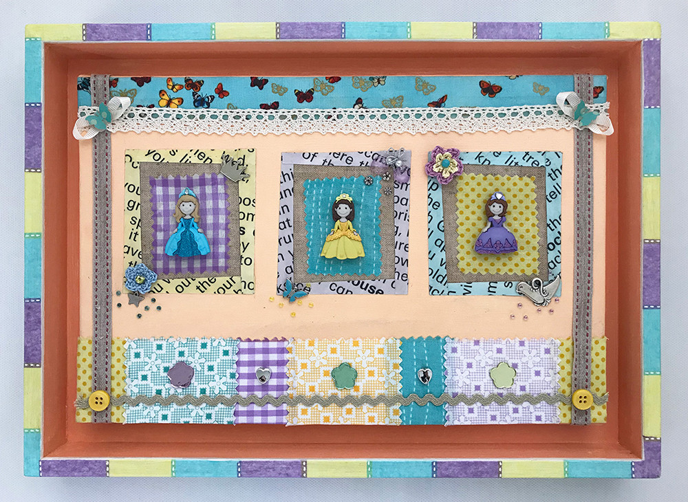 mixed media art with little princesses. an assemblage with paper, fabrics, buttons and beads in yellow, purple, turquoise and peach colour. Completed with a matching decoupaged frame.