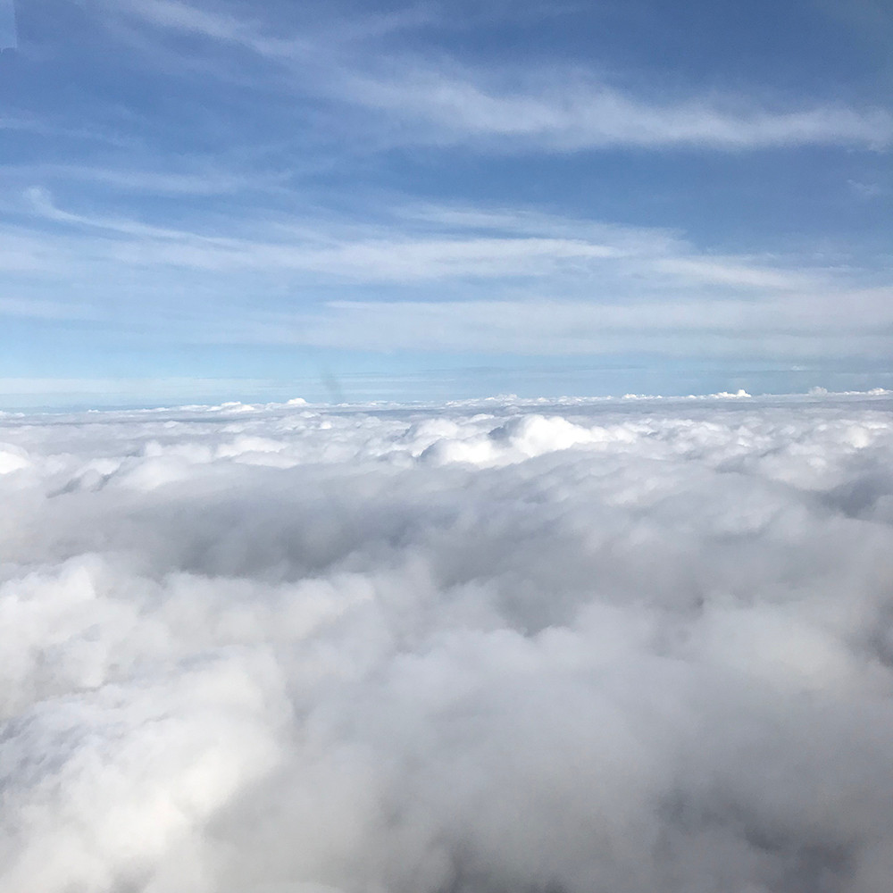 Looking down at clouds and blue sky. Aeroplane view.