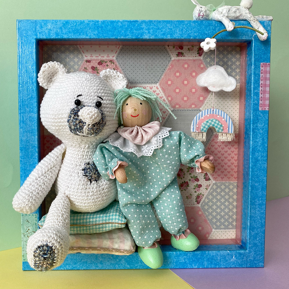 Shadow box mixed media art for the baby room or the playroom. It features a handmade fabric doll and it friend a crochet bear.
