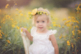 Young girl sitting in wildflowers near Marana AZ for her photography session