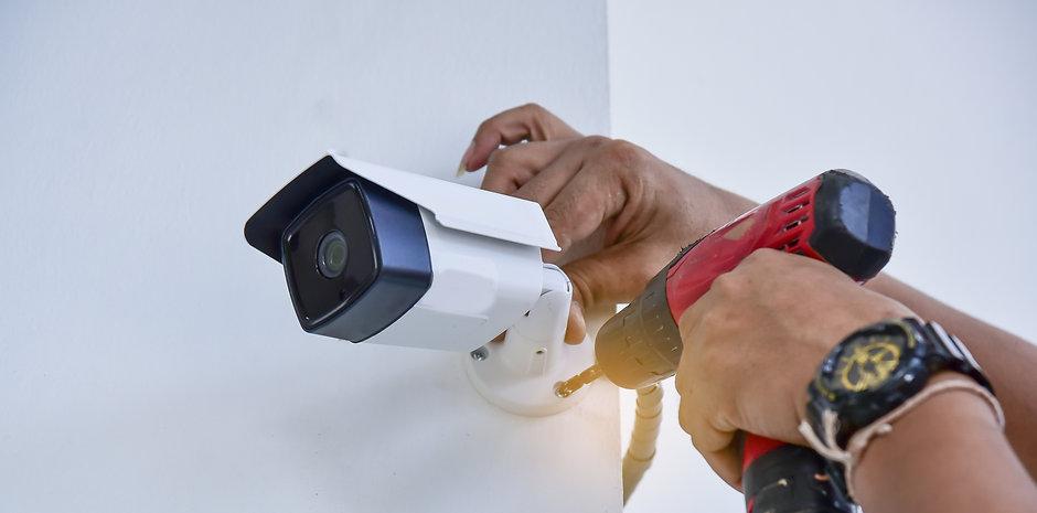 Technician installing CCTV camera for se