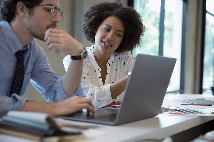young professional african american woman working with a young professional white man in an office. consilium.