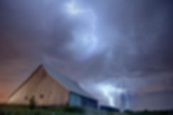 A barn at night with lightning strikes.